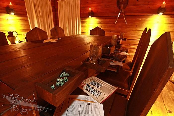 Gavetas da mesa aberta. Dados, canecas e fichas em cada suporte da mesa.